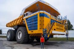 World&#x27 μεγαλύτερο τεράστιο φορτηγό BelAZ του s με το άτομο για την κλίμακα στοκ εικόνα