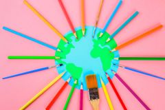 World art. Planet Earth and pencils, brushes on a pastel pink background. World art. Planet Earth and pencils, brushes on a pastel pink background stock photo