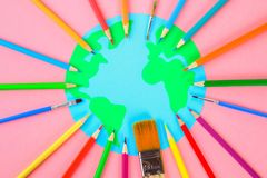 World art. Planet Earth and pencils, brushes on a pastel pink background. World art. Planet Earth and pencils, brushes on a pastel pink background royalty free stock image