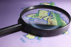 World atlas. World map with a magnifying glass on a purple background Stock Photos