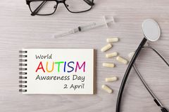 World Autism Awareness Day Concept. World Autism Awareness Day 2 April written on notebook with stethoscope,syringe,eyeglasses and pills on wooden desk. Medical Royalty Free Stock Photo