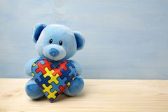 World Autism Awareness day, concept with teddy bear holding puzzle or jigsaw pattern on heart. World Autism Awareness day, mental health care concept with teddy stock images