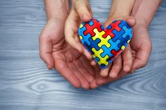 World Autism Awareness day, puzzle or jigsaw pattern on heart with autistic child`s and father hands. World Autism Awareness day, mental health care concept with royalty free stock photo