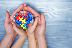 World Autism Awareness day, puzzle or jigsaw pattern on heart with autistic child`s and father hands. World Autism Awareness day, mental health care concept with stock images