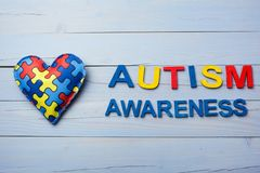 World Autism Awareness day, mental health care concept with puzzle or jigsaw pattern on heart. On blue woodend background stock photography