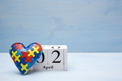 World Autism Awareness day, mental health care concept with puzzle or jigsaw pattern on heart with calendar. On blue, wooden background royalty free stock images