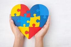 World Autism Awareness day, mental health care concept with puzzle or jigsaw pattern on heart with child`s hands. On white wooden background royalty free stock photos