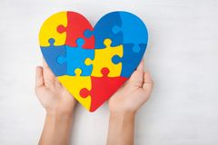 World Autism Awareness day, mental health care concept with puzzle or jigsaw pattern on heart with child`s hands. On white wooden background Stock Photos