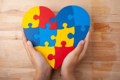 World Autism Awareness day, mental health care concept with puzzle or jigsaw pattern on heart with child`s hands. On wooden background Royalty Free Stock Photography