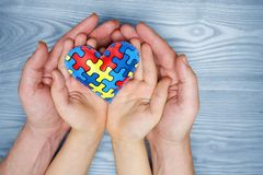 World Autism Awareness day, puzzle or jigsaw pattern on heart with autistic child`s and father hands. World Autism Awareness day, mental health care concept with stock photos