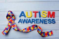 World Autism awareness and pride day or month with Puzzle pattern ribbon on blue wooden background. World Autism awareness and pride day or month with Puzzle stock images