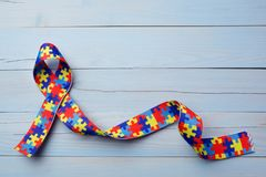 World Autism awareness and pride day or month with Puzzle pattern ribbon on blue wooden background. World Autism awareness and pride day or month with Puzzle royalty free stock photos