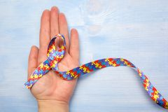 World Autism awareness and pride day with Puzzle pattern ribbon on hand. World Autism awareness and pride day with Puzzle pattern ribbon and hand on wooden royalty free stock photo