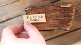 The World Awaits idea. Travel idea. The World Awaits text and old book stock video