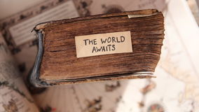 The World Awaits idea. Traveler idea. The World Awaits text, old book and old geographic map stock video