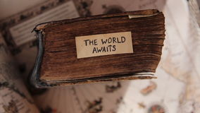 The World Awaits idea. Traveler idea. The World Awaits text, old book and old geographic map stock footage