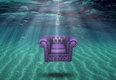 A world awaits. Surreal underwater scene with floating chair and hanging keys Stock Photo