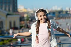 The world beyond my headphones is too chaotic. Little girl wearing headphones on urban outdoor. Cute child listening to. Music in ear stereo headphones royalty free stock images