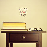 World book day, with a retro effect. Black eyeglasses and some books on a table and the sentence world book day on a beige background, with a retro effect Royalty Free Stock Photos