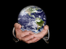 World of business. Hands holding an earth planet against a black isolated background Stock Photos