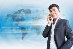 World Of Business Connection. Asian Businessman Talking On The Phone With Friendly Smile Royalty Free Stock Photography