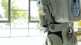 Close up of robot walking in office. The world is calling. Called up look on an illuminating robotic machine walking around the office and going toward a stock video