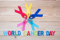 World cancer day February 4. colorful awareness ribbons; blue, red, pink and yellow color on wooden background for supporting royalty free stock photo