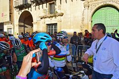 The World Champion Talks With Race Director in The Streets Of Alicante. Alejandro Valverde wearing he rainbow shirt of the World champion, waits in the narrow stock photo