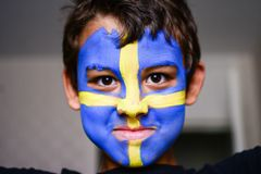 World Championship in football 2018 face painting on boy. World Championship in football 2018 Beautiful Swedish flag painted on the face of a boy, who is super stock photo