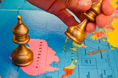 World chess australia bishop move. A map of australia with a bishop on it, and a hand moving another bishop piece Stock Photography