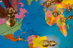 World chess usa move. A queen chess piece held over the nation of USA, with the other pieces in the world in the background royalty free stock images