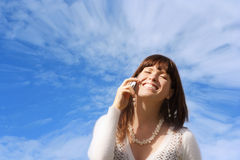 World of communication. Young girl with phone against blue sky Stock Images