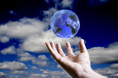 World concept. Abstract earth hoovering over an open hand with sky background Stock Image