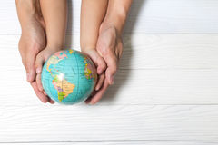 World concept: Two human hands holding global on wooden backgrou Stock Image