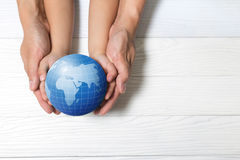World concept: Two human hands holding global on wooden backgrou Royalty Free Stock Photos