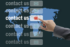 World contact us. Male business hand pushing on contact us button with world map background Stock Image