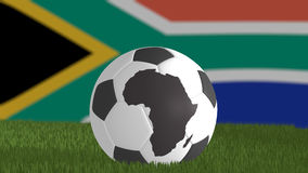 World cup 2010 South Africa theme. With a soccer ball with the Africa continent.  The South African flag is out of focus on the background Royalty Free Stock Images
