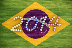 World Cup 2014. 3D rendering of footballs form in to the year 2014 over a Brazil flag painted on a wood floor Stock Photo