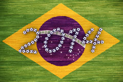 World Cup 2014. 3D rendering of footballs form in to the year 2014 over a Brazil flag painted on a wood floor Royalty Free Stock Images