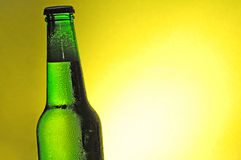 World cup football green beer bottle. Green see through bottle of beer with tiny clear drops on its surface. The liquid has a small layer of white foam up to the Royalty Free Stock Photo