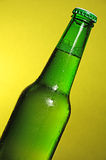 World cup football green beer bottle. Green see through bottle of beer with tiny clear drops on its surface. The liquid has a small layer of white foam up to the Royalty Free Stock Photography