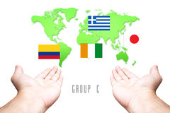 World Cup 2014 Group-C Flag with Hand and World Map background Stock Photography
