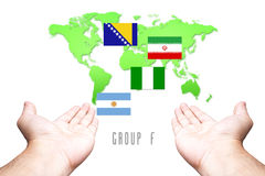 World Cup 2014 Group-F Flag with Hand and World Map background Royalty Free Stock Image