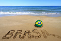 World cup. Soccer ball with Brazilian flag and word Brasil written on the beach Stock Image