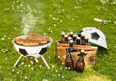 World Cup Soccer themed barbecue with beers. World Cup Soccer themed barbecue with meat grilling on a ball shaped BBQ and box of bottled craft beers in a green royalty free stock image