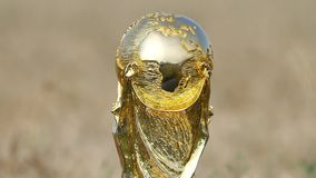World cup trophy. Rotating against a golden background stock footage