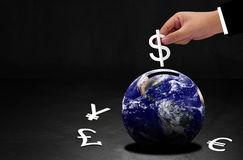 World Currency Concept. Global financial success, hand of business man holding white paper cut dollar symbol and earth, Elements of this Image Furnished by Stock Photos