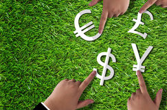 World Currency Concept. Global financial success, hand of business man holding white paper cut dollar, yen, euro and pound symbol on green grass background Royalty Free Stock Photos