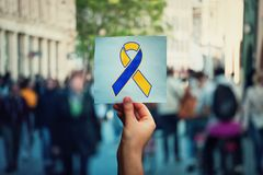 World Down Syndrome day as hand holding a paper sheet with blue yellow awareness ribbon symbol over crowded street background royalty free stock photo