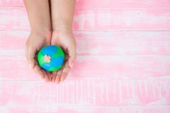 World Earth Day concept. Woman hand holding handmade globe. On white and pink pastel wooden table background texture stock image